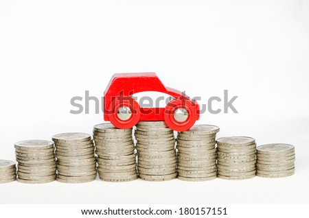 piles of coins and a car - stock photo