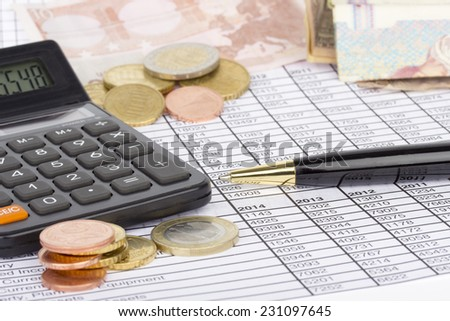Piles of coins with calculator and pen on paper with financial situation - stock photo