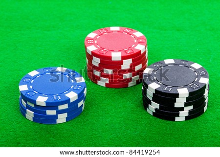 piles of colorful casino chips on green table