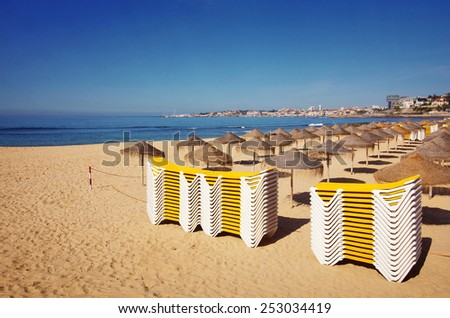 Piles of deck chairs in a beach in Estoril, Portugal - stock photo