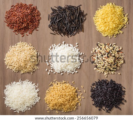 Piles of different rice varieties over a wooden background including jasmine, basmati, wild rice, risotto and parboiled in Red, white, brown and black.