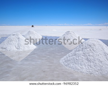 Piles of drying salt and reflection in the water at the Salar de Uyuni (salt flats) in Bolivia. - stock photo