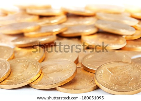 Piles of gold coins spread over a table - stock photo