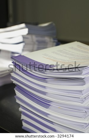 Piles of handout papers lying on a table. - stock photo