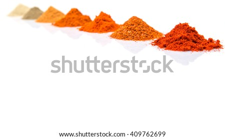 Piles of hot and spicy spices powder, cayenne powder, chilly powder, peppercorn powder, paprika powder, black pepper and white pepper powder over white background - stock photo