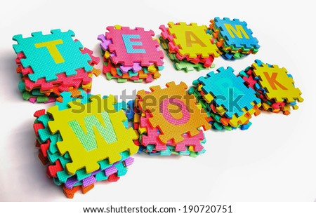 piles of jigsaw letter arranged as teamwork - stock photo