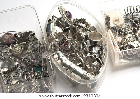 Piles of miscellanious silver jewelry in transparent boxes.