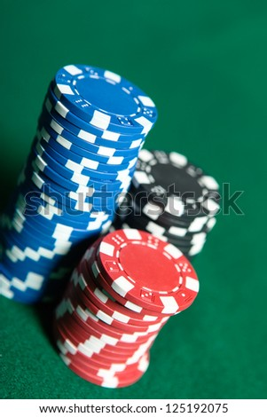 Piles of multicolored chips on the green poker table. Risky entertainment of gambling - stock photo