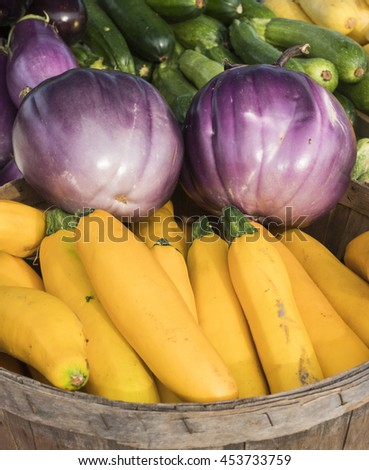 Piles of squash, eggplants, and cucumbers at local farm market. - stock photo