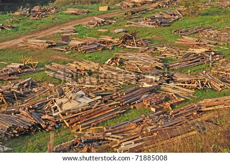 Piles of wooden logs and boards on the ground, broken decoration after filming