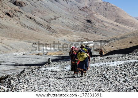 Pilgrims circumambulating Mt. Kailash by performing full body prostrations, Western Tibet - stock photo