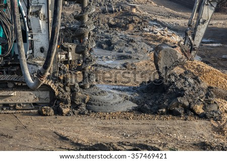 Piling rig installs concrete piles, machines pouring concrete into excavated deep foundation pile. Piling drill rig at construction site. Selective focus. - stock photo
