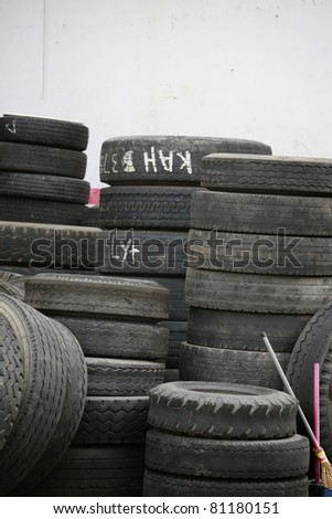 piling up of used up truck tyres on white wall