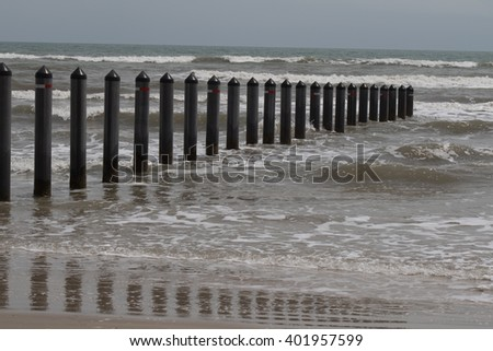 Pilings on shoreline stretching into the surf (left to right) - stock photo