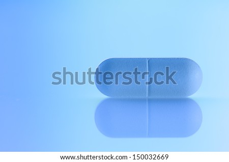 Pill against blue background - stock photo