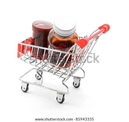pill bottle in shopping cart trolley - stock photo
