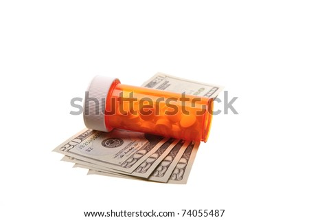 pill bottle laying on cash - stock photo