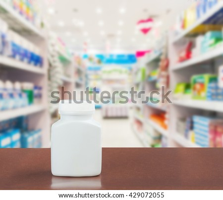 Pill bottle on table top on blurred pharmacy, Pharmacy in shopping mall, Pharmacy in shopping center, Shopping drug and pill at pharmacy in holiday - stock photo