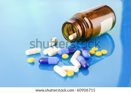 Pill bottle with coloured pills on blue - stock photo