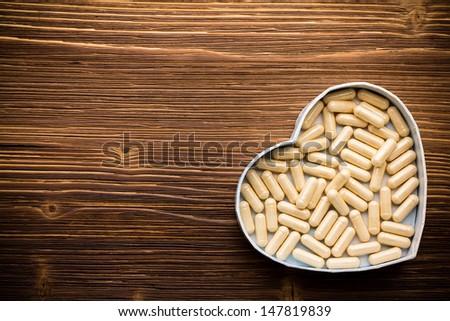 Pill, heart-shaped box. Wooden surface. - stock photo