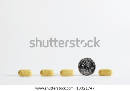 Pill in a line with quarter - stock photo