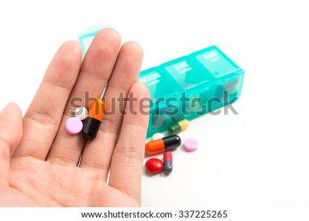 Pill in hand and medicine dose box - stock photo