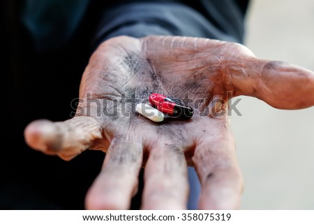pill in the hands of the poor old man. - stock photo
