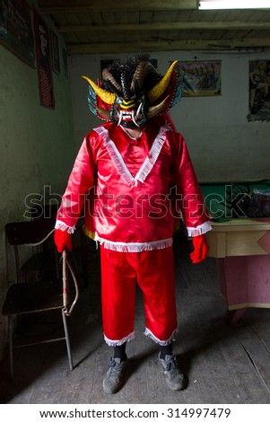 PILLARO, ECUADOR - JANUARY 4, 2014: Unknown man dressed as the devil in the Diablada, popular town celebrations with people dressed as devils dancing in the streets - stock photo