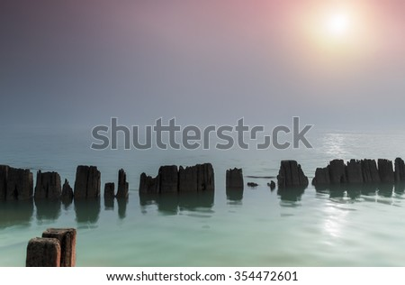 Pillars in water in a foggy morning