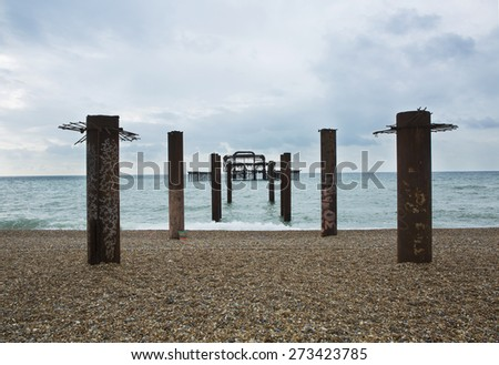 Pillars on the beach facing the abandoned and derelict West Pier in Brighton, UK - stock photo