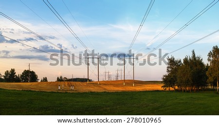 Pillars with high-voltage electric wires over the field after harvest in the countryside. Scenic landscape at sunset. Panoramic shot. - stock photo