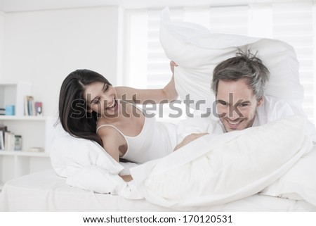 pillow fight for a young couple in bed