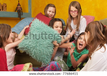 Pillow-fighting among seven girls at a sleepover - stock photo