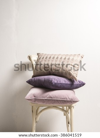 pillow on the chair behind white wall interior concept - stock photo