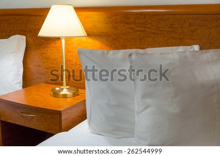 Pillows and lamp in hotel room - stock photo
