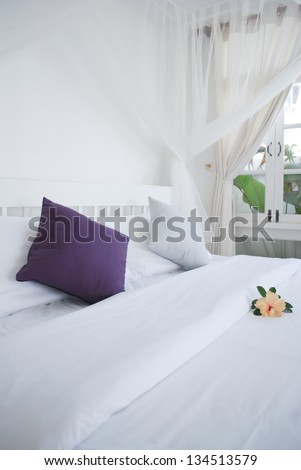 pillows and white bed in white bedroom - stock photo