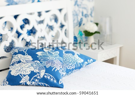 Pillows closeup in nicely decorated bedroom in blue and white colors - stock photo