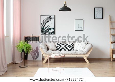 beige sofas living room. Pillows on beige sofa against wall with posters in simple living room  copper table and On Beige Sofa Against Wall Stock Photo Royalty Free
