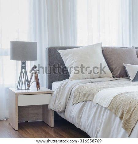 pillows on modern bed with grey lamp on wooden table side in modern bedroom - stock photo