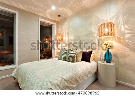 Pillows on the master bed near to the cylinder shaped table or stool. There two lamps hanging over the bed and near to the wall. The cover of them are made of rattan. When the lights turned on,