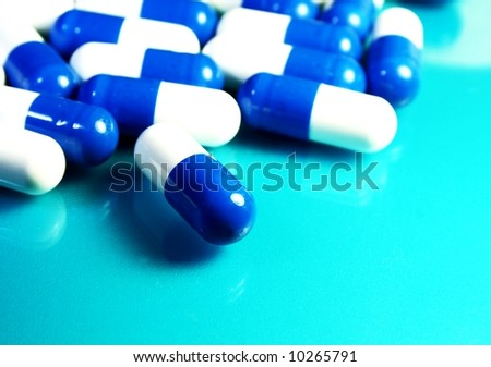 pills against a blue background - stock photo
