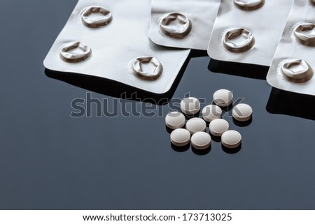 Pills and bubble-packed Aluminum Foils on Glass Background - stock photo