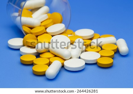 Pills and capsules spilling from a medicine cup.