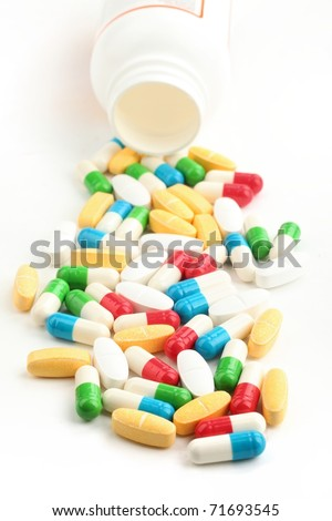 Pills and capsules with open bottle - stock photo