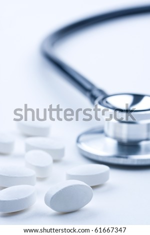 Pills and doctor's stethoscope.  Concept of healthcare. - stock photo