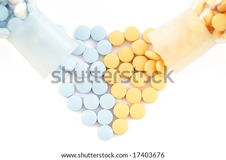 pills and drugs forming heart on white - stock photo