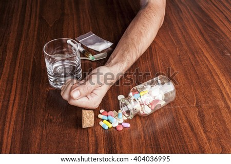Pills and drugs with empty glass and hand on brown wood table - stock photo