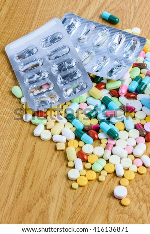 pills and empty blister pack on to surface wooden background - stock photo