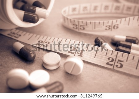 pills and measuring tape (lose weight concept)