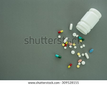 pills and pill bottle on gray background. top view. - stock photo